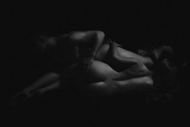 Nahý muž a žena v objatí v tme