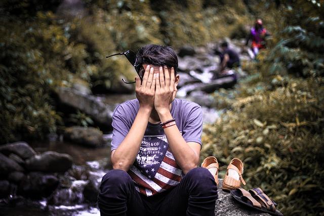 Mladý muž si zakrýva tvár, príroda