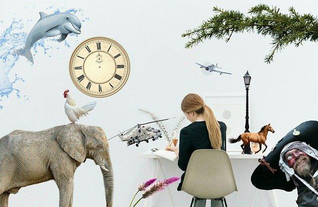 Žena sedí pri stole, píše a je obklopená abstraktnými obrázkami