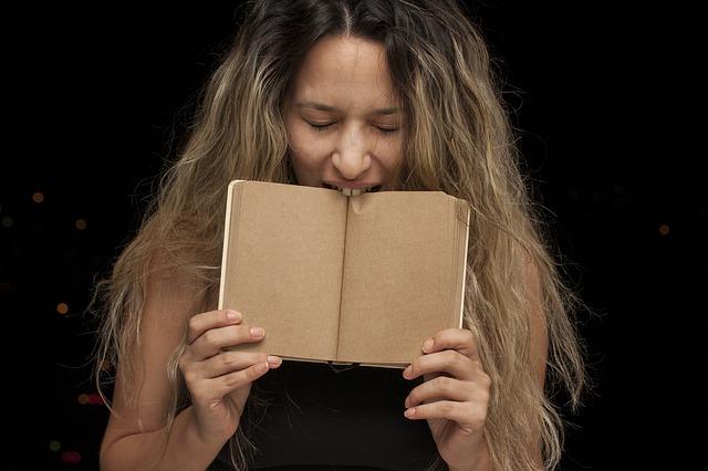 Žena s dlhými vlasmi hryzie do knihy